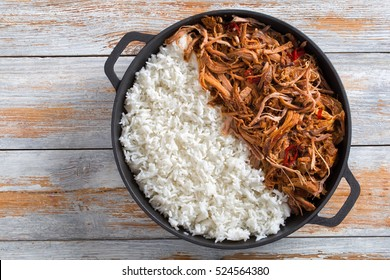 pulled slow-cooked pork shoulder grilled in oven with basmati rice in iron frying pan on wooden table, view from above