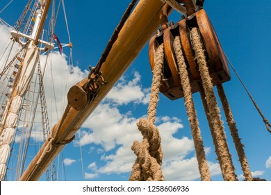 Pulley on a large sailing ship in front of vivid blue sky with white clouds