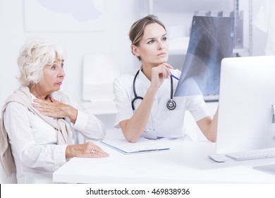 Pulmonologist analyzing senior patient's chest x-ray picture