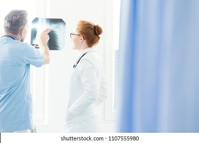 Pulmonologist consulting on an X-ray image with another doctor in the hospital