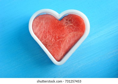 Pulp of watermelon inside the mold in the form of a heart. Blue wood background. View over. Close-up. Macro photography.