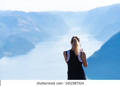 PULPIT ROCK, NORWAY - JULY 26, 2018: Unknown female tourist enjoying the stunning view over the Lysefjord from Pulpit Rock. The Pulpit Rock or Preacher's Chair is a tourist attraction in Forsand