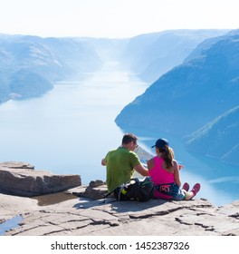 PULPIT ROCK, NORWAY - JULY 26, 2018: Couple enjoying the stunning view on Pulpit Rock. The Pulpit Rock or Preacher's Chair is a tourist attraction in the municipality of Forsand in Rogaland county