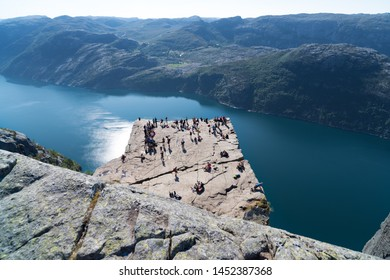 PULPIT ROCK, NORWAY - JULY 26, 2018: Tourists enjoying the stunning view on Pulpit Rock. The Pulpit Rock or Preacher's Chair is a tourist attraction in the municipality of Forsand in Rogaland county