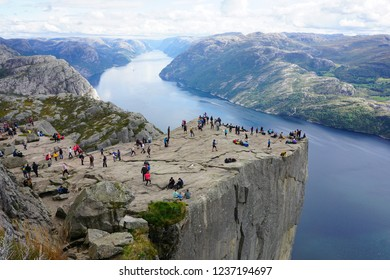 Pulpit Rock (Preikestolen) in Norway with lots of people on a cloudy day of summer