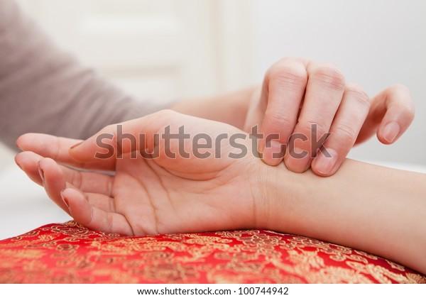 Pulsdiagnose mit Hand auf einem Polster