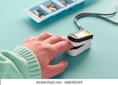 Pulse Oximeter, finger digital device to measure person's oxygen saturation. Reduced oxygenation is an emergency sign of pneumonia, for instance caused by coronavirus. Device on Caucasian female hand.