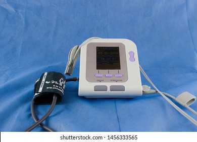 A pulse oximeter and a kit for measuring pressure for a newborn baby on a blue medical sheet background. Preparation for surgery or other surgery for a minor child