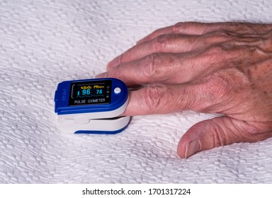 Pulse oximeter on finger used to test blood oxygen level in case of virus infection of the lungs with senior hand resting on bedspread