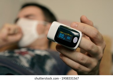 pulse oximeter on a mans finger. oxygen saturation of the blood. A patient in a medical mask measures blood saturation with an electronic pulse oximeter on his finger. low saturation of the blood.