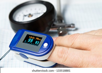 A pulse oximeter used to measure pulse rate and oxygen levels with Sphygmomanometer and ECG background