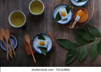 Pulut Tai Tai. Peranakan blue glutinous rice cake with kaya jam. Lined with bamboo leaf and plated individually on a ceramic saucer of matching color.
