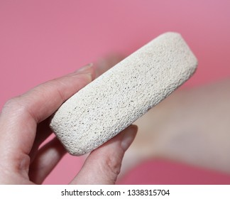 Pumice stone for foot care. In the photo a woman's hand holds a pumice near the heel of her foot. Removal of rough skin on the heels of the feet with the help of pumice. Pink background.