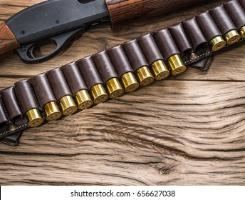 Pump action shotgun, 12 guage cartridge on the wooden table.