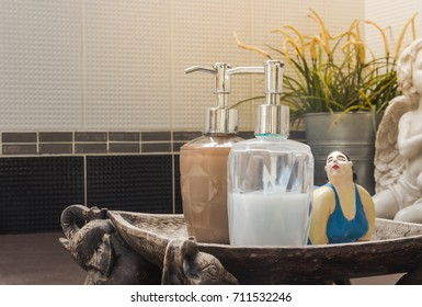 Pump glass bottle with liquid soap on wood tray in a bathroom and yellow flower plant decorate in background.vintage style.