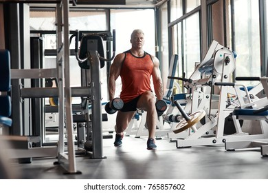 Pump iron. Waist up of a strong man doing squats with dumbbells in his hands while training in the gym