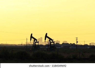 pump jack silhouettes against city skyline and golden light