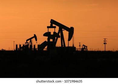 Pump jacks silhouette at sunset