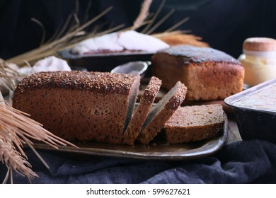 Pumpernickel sliced bread with seeds on rustic wooden kitchen table.