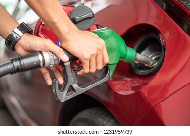 Pumping equipment gas at gas station. Close up of a hand holding fuel nozzle