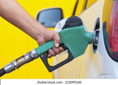 Pumping gas at gas pump. Closeup of man pumping gasoline fuel in car at gas station