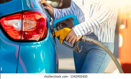 Pumping gas at gas pump. Woman refuel the car. Woman  at the petrol station. Woman filling her car with petrol at gas station. Pumping fuel in to the tank. Detail Of woman Filling Car With Diesel