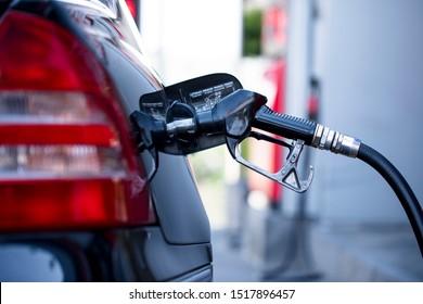 Pumping gasoline fuel in black car at gas station , Gas pump nozzle.