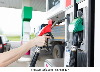 Pumping gasoline fuel in black car at gas station