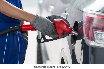 Pumping gasoline fuel in car at gas station.The hand holds the refueling gun