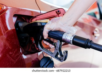 Pumping gasoline fuel in car at gas station.The woman hand holds the refueling gun