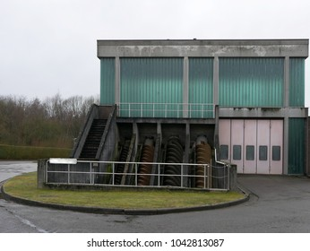 Pumping station with screw of archimedes. Full view on jumpstation with collection of archimedes screws and cloudy sky