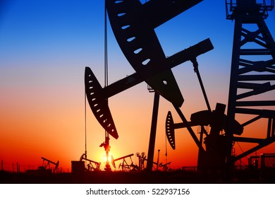 Pumping unit in the work, under the sunset of oilfield