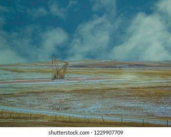 Pumpjack, Nodding Donkey, in winter field near Dickinson, North Dakota