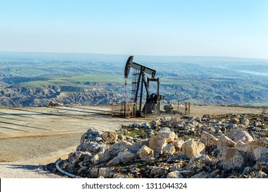 A pumpjack in the oil well. A pumpjack converts the rotary motion of the motor to a vertical reciprocating motion to drive the pump shaft, which is exhibited in the characteristic nodding motion.