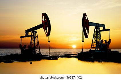 Pumpjack on the beach at sunset.