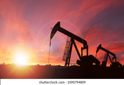 Pumpjack silhouette against a sunset sky with deliberate lens flare and copy space. These jacks can extract between 5 to 40 litres of crude oil and water emulsioin at each stroke.