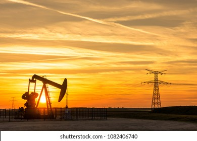 Pumpjack and transmission towers at sunset symbolizing energy transition. The setting sun is passing between the posts of a pumpjack in France with electricity pylons and power line against a red sky.