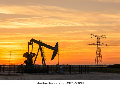 Pumpjack and transmission towers at sunset symbolizing energy transition. A pump jack pumping oil out of a well in France with silhouettes of electricity pylons and power line against a red sky.