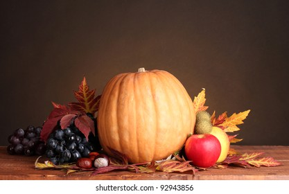pumpkin, apples, grapes and leaves on wooden table on brown background
