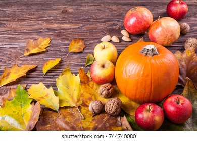 Pumpkin, apples and walnuts on a wooden table