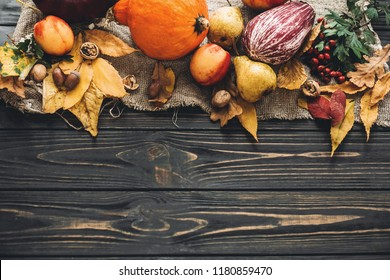 Pumpkin, autumn vegetables with colorful leaves,acorns,nuts, berries on wooden rustic table, flat lay with space for text. Fall seasons greeting card. Happy Thanksgiving. Hello Autumn
