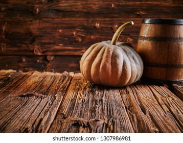 Pumpkin and barrel on old wooden table with aged wood grain surface inside rustic house. Copy space