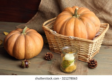 pumpkin in the basket and the candle with chestnuts on a wooden table