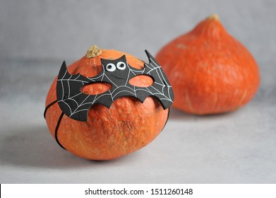 Pumpkin in batman's mask. Behind her is another pumpkin. Halloween holiday attribute. Close-up. Grey background.