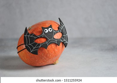 Pumpkin in batman's mask. Halloween holiday attribute. Close-up. Free space for text. Grey background.