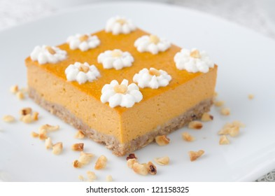 Pumpkin cake, decorated with flowers made of whipped cream and nuts, closeup