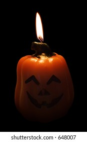 Pumpkin candle with flame isolated on white background