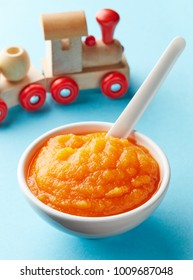 Pumpkin and carrot baby puree in bowl with baby spoon and toy train on blue background