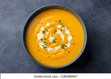 Pumpkin, carrot cream soup in a bowl. Slate background. Top view.