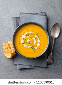 Pumpkin, carrot cream soup in a bowl. Grey background. Top view.